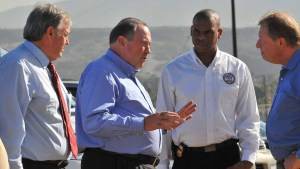 Gov. Mike Huckabee with former Rep. Duncan Hunter (left) speaks with representatives of border patrol union Terence Shigg (second from right) and Chris Harris (right). Photo by Chris Stone