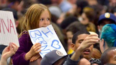 A young girl holds a sign at Sanders rally. Photo by Chris Stone