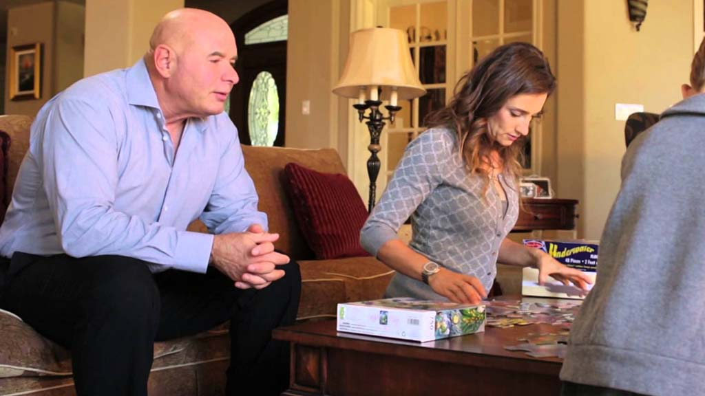 Leo Hamel watches family assemble a puzzle in scene from TV commercial.