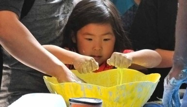 Children sunk their hands into a combination of corn starch and colored water. Photo by Chris Stone