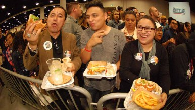 The Plata family of North Park (from left, Gilberto, Gilbert and Judith) feasted on concession burgers and fries while awaiting Sanders arrival. Photo by Ken Stone