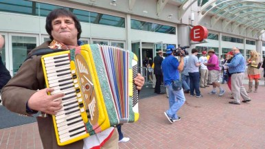 Accordion player Shalom Sherman entertained outside the Convention Center and handed out cards. Photo by Ken Stone