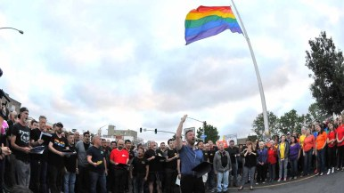 The director of the San Diego Gay Men's Chorus leads the crowd in song at the foot of the Hillcrest Pride Flag. Photo by Chris Stone