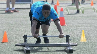 A USS Essex team member pushes a weight sled at NFL Boot Camp. Photo by Chris Stone