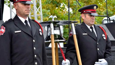 Firefighters ring a bell in honor of fallen first responders. Photo by Chris Stone