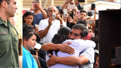 People in Mexico document the visits as Eduardo Hernandez hugs his son, Luis, at Border Field State Park. Photo by Chris Stone