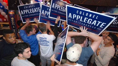 Supporters of Doug Applegate display signs behind GOP Rep. Darrell Issa during one of his broadcast interviews. Photo by Ken Stone