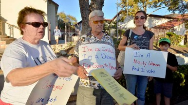 Linda Kleiner, Les Kleiner and Lindsay Krosby protest outside Immaculate Conception Catholic Church. Photo by Chris Stone