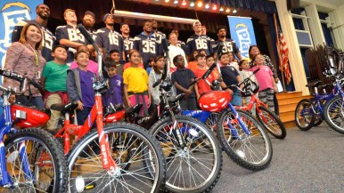 Classes and their teachers pose with Chargers players at bike giveaway at Baker Elementary School. Photo by Chris Stone