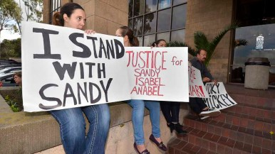 For part of the two-hour protest, sign-holders sat at the entrance of the United Labor Center. Photo by Ken Stone