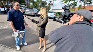 Protest organizer Brent Beltrán speaks to CBS8 reporter Ashley Jacobs before a quiet demonstration. Photo by Ken Stone