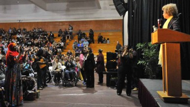 A Muslim woman stands and applauds Angela Davis after a speech at Southwestern College. Photo by Chris Stone