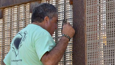 Enrique Morones, founder of Border Angels, speaks through the fence to Mexican citizens. Photo by Chris Stone