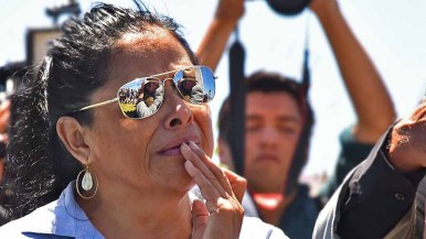 A relative of Jannet Fernandez Vargas waits to give her a hug, as the embrace of daughter and father is reflected in her glasses. Photo by Chris Stone