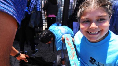 A child is excited about a gift she receives from Border Angels. April 30 is Children's Day in Mexico. Photo by Chris Stone