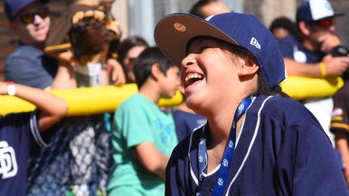 A young fan laughs as she misses a pitch in a wiffle ball game at Padres FanFest. Photo by Chris Stone