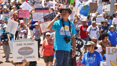 A young man takes a call while standing on fire hydrant amid People's Climate March San Diego. Photo by Ken Stone