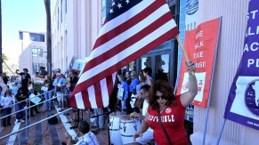 Woman in Indivisible shirt waved Old Glory throughout pre-march rally on steps of County Administration Center. Photo by Ken Stone