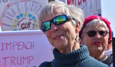 The protest is reflected in the sunglasses of a woman by the Hotel del Coronado where the RNC is holding its spring meeting. Photo by Chris Stone