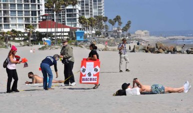Protesters set up staging area by the Hotel Del Coronado as men sunbathe nearby. Photo by Chris Stone