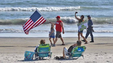 A member of Indivisible and another protester with a sign march in front of a couple soaking up the sun on the beach adjacent to the Hotel del Coronado, where the RNC is holding its spring meeting. Photo by Chris Stone