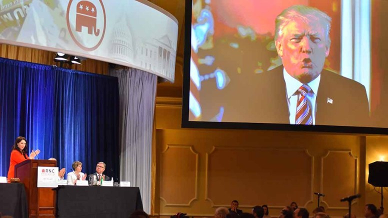 Republican National Committee Chairwoman Ronna McDanie (in red) applauds President Trump in video shown at RNC meeting at the Hotel del Coronado. Photo by Ken Stone