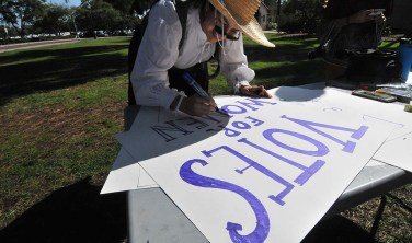 Angela Castillo of San Diego readies a sign for the woman's suffrage march in Balboa Park.