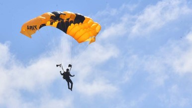 A member of the Army Golden Knight Parachute Team descends from the sky.