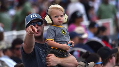 A man and his child watch the Blue Angels perform at the Miramar Air Show.