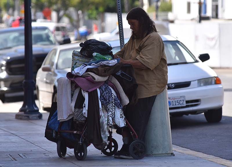 The homeless in downtown San Diego move along streets with their belongings.