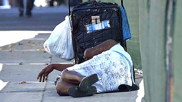 A homeless woman sleeps on the sidewalk