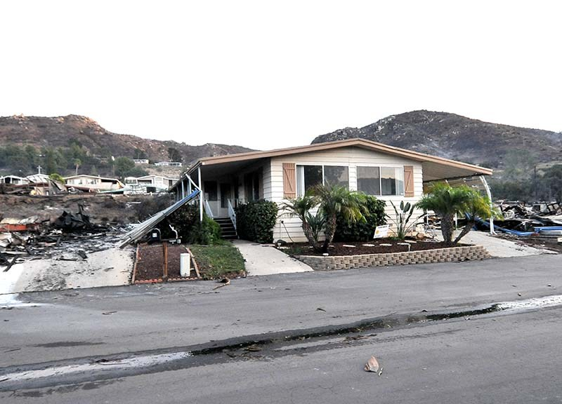 One mobile home stands while others on both sides and behind it burned at the Rancho Monserate Country Club.