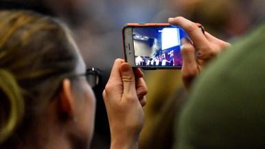 An audience member records the gubernatorial debate.