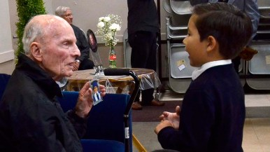 A young boy shares his photo by Fr. Brown at his farewell dinner.