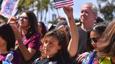 A young woman show solidarity with speakers at the rally against gun violence. Photo by Chris Stone
