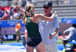 Hawaii coach Tim Boyce congratulates Lily Lowe during her personal-record meet.