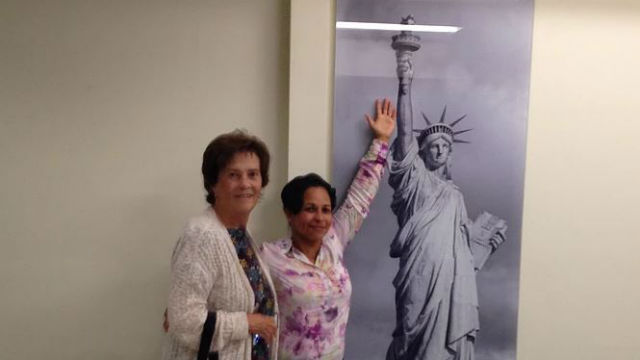 Immigrant with poster of the Statue of Liberty