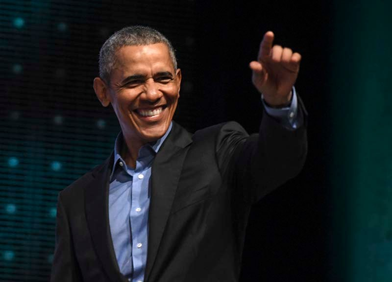 President Obama signals to as many as 11,000 people as he arrives for talk at San Diego Convention Center.