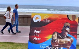 Joggers, cyclists and skateboarders pass by scene of ANOC World Beach Games press conference in Mission Beach.
