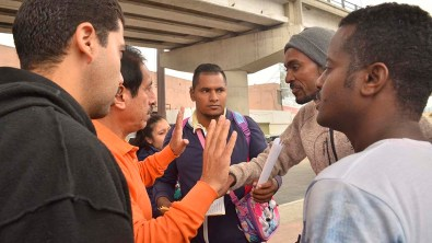 An African immigrant, who believes that he lost his place in line, argues with a Mexican official.