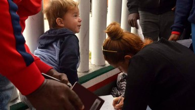 A toddler sits at the gate as a woman adds her family's name to the waiting list to seek asylum.