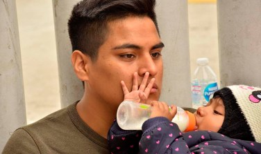 A man who wasn't on the list to enter the U.S. on Saturday holds an infant and waits.