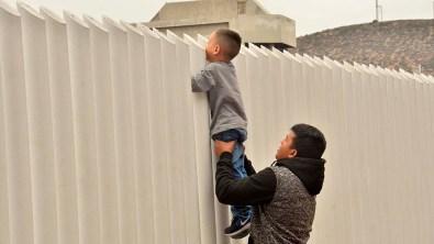 A man holds up a child who peeks into U.S. territory.