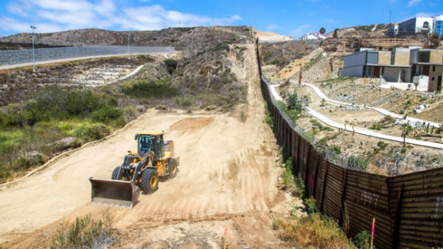 Bulldozer prepares ground for border fence replacement