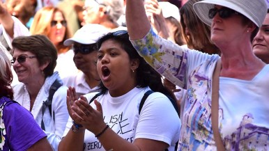 A protestor applauds remarks by Border Angel founder Enrique Morones at a Families Belong Together rally a Waterfront Park.