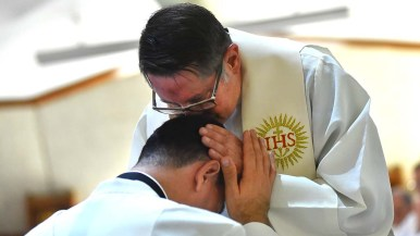 A Jesuit priest kisses the top of O. Alejandro Baez-C Gonzalez. All priests filed by those who were ordained and laid their hand on them.