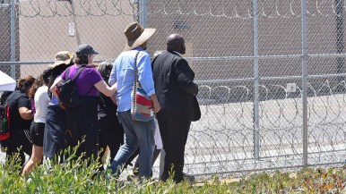 The Rev. Ben McBride leads protesters into the detention center parking lot despite orders by guards to stop.