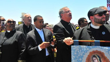 San Diego Catholic bishops Robert McElroy (second from left) and John Dolan (fourth from the left) listen to the cheers coming from within the detention center.