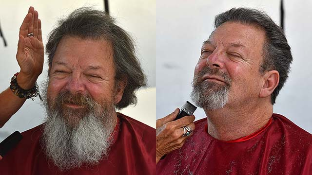 Twenty-year Navy veteran Marvin Pfeffer, 60, gets a haircut and beard trim at Stand Down at San Diego High School.