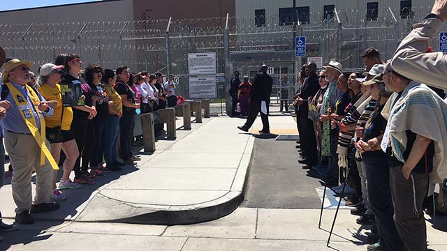 Religious leaders lock arms in the streets outside the Otay Mesa detention center.